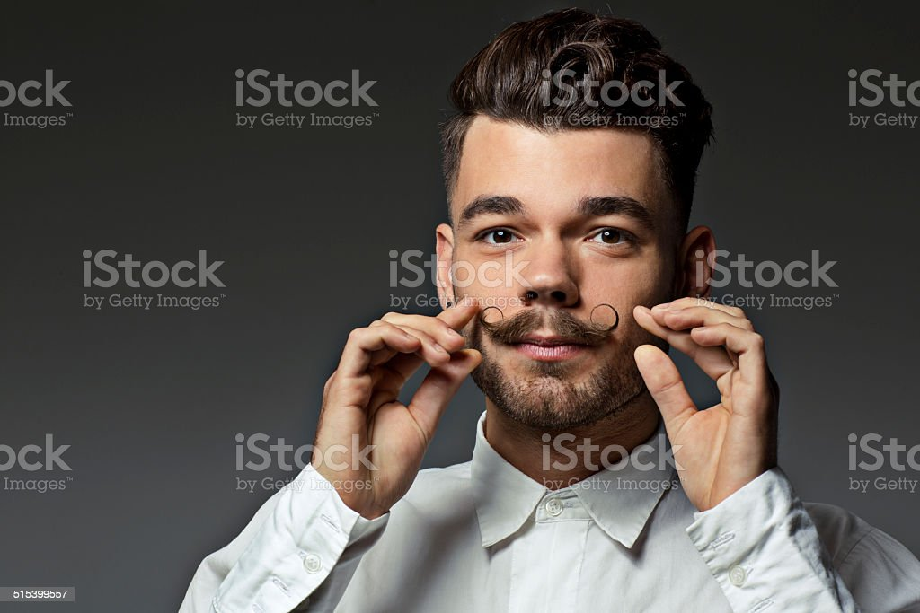 portrait of young man touching his  moustaches stock photo