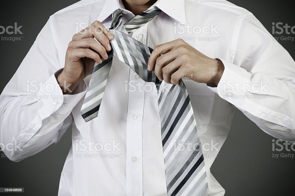 Portrait of young man tying a tie royalty-free stock photo