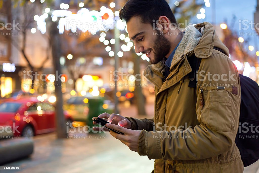 Portrait of young man using his mobile phone at night. stock photo