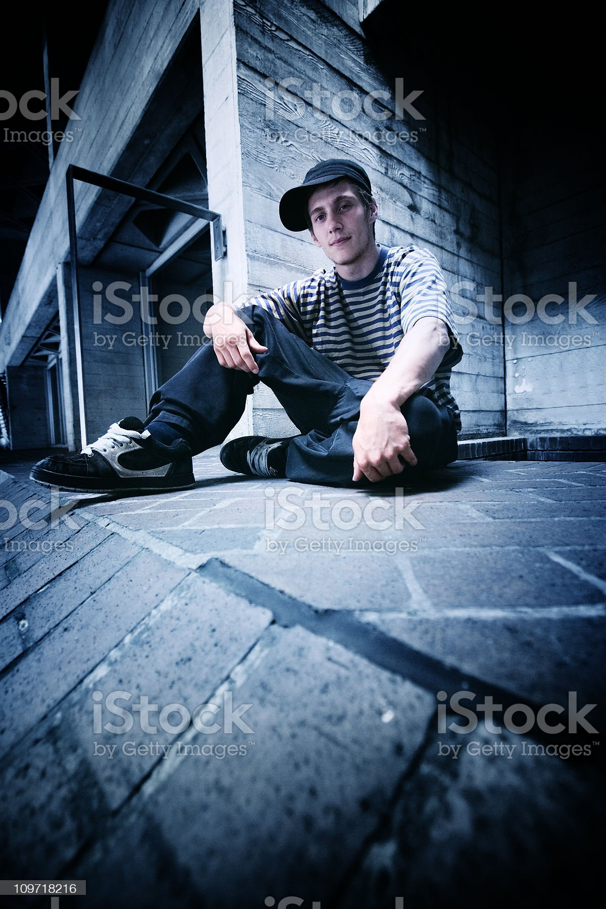 Portrait of Young Man Wearing Casual Clothes Sitting on Ground royalty-free stock photo