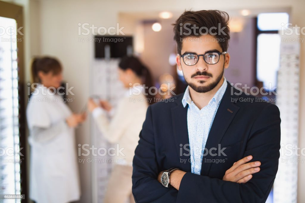 Portrait of young man wearing eyeglasses in optical store stock photo