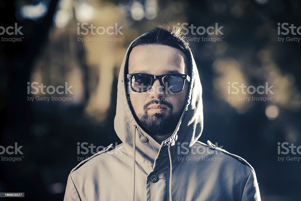 Portrait of young man wearing hood and sunglasses royalty-free stock photo
