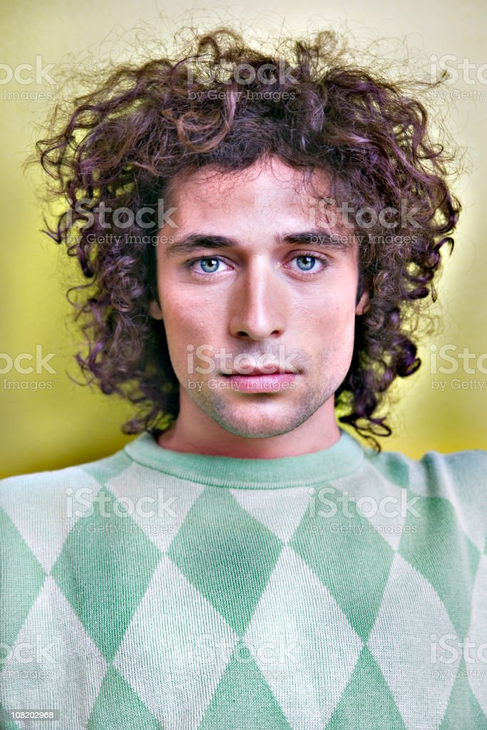 Portrait of Young Man with Curly Hair Looking at Camera royalty-free stock photo