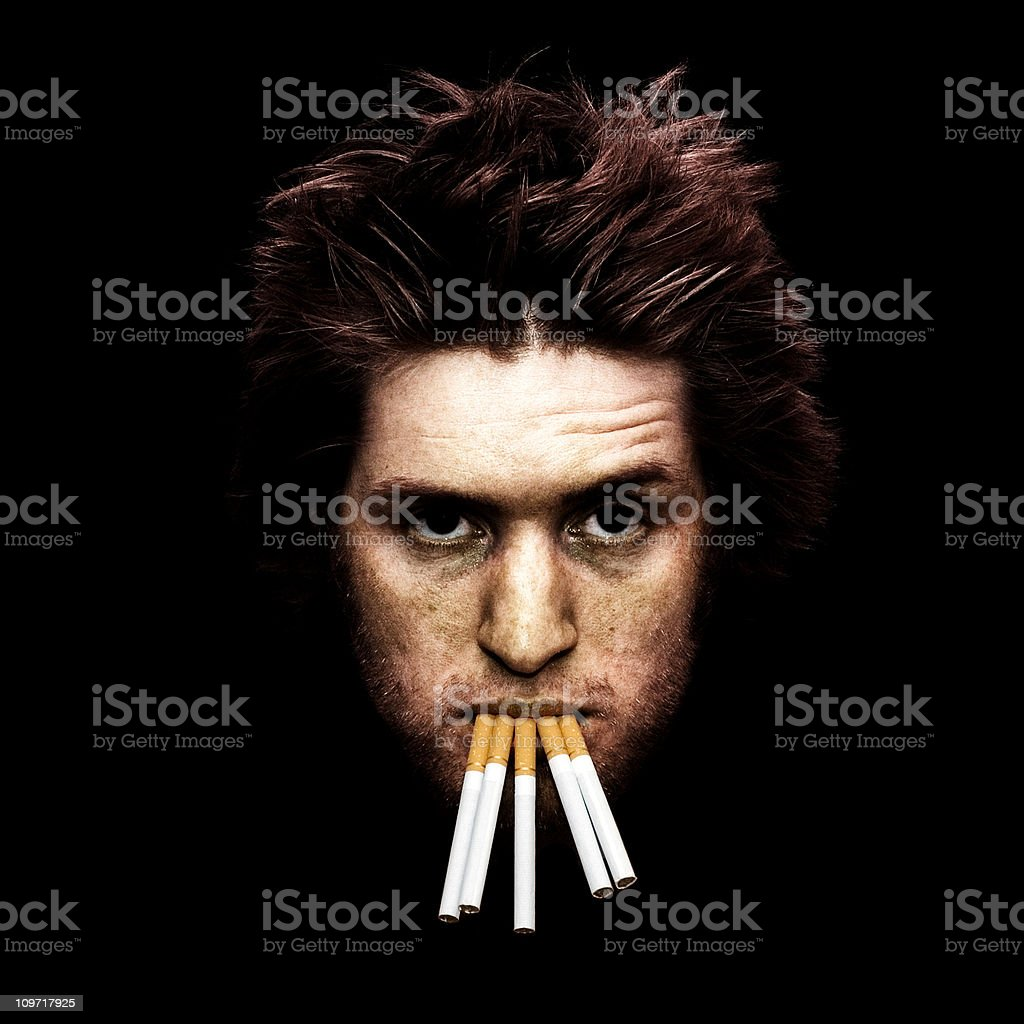 Portrait of Young Man with Many Cigarettes in Mouth royalty-free stock photo