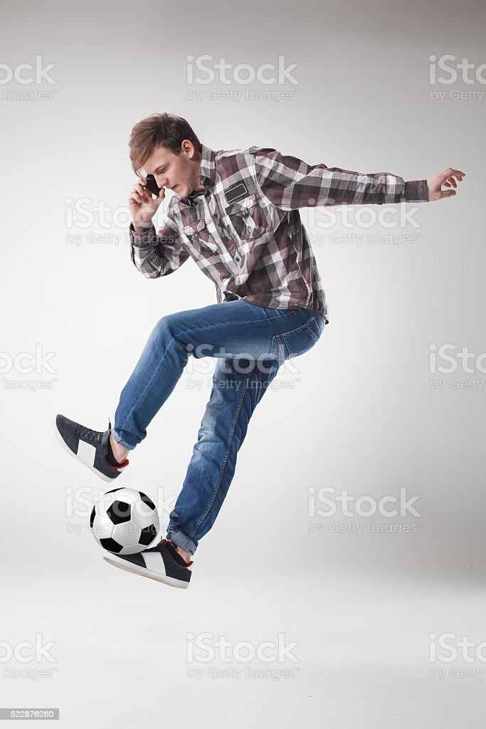 Portrait  of young man with smart phone and football ball stock photo