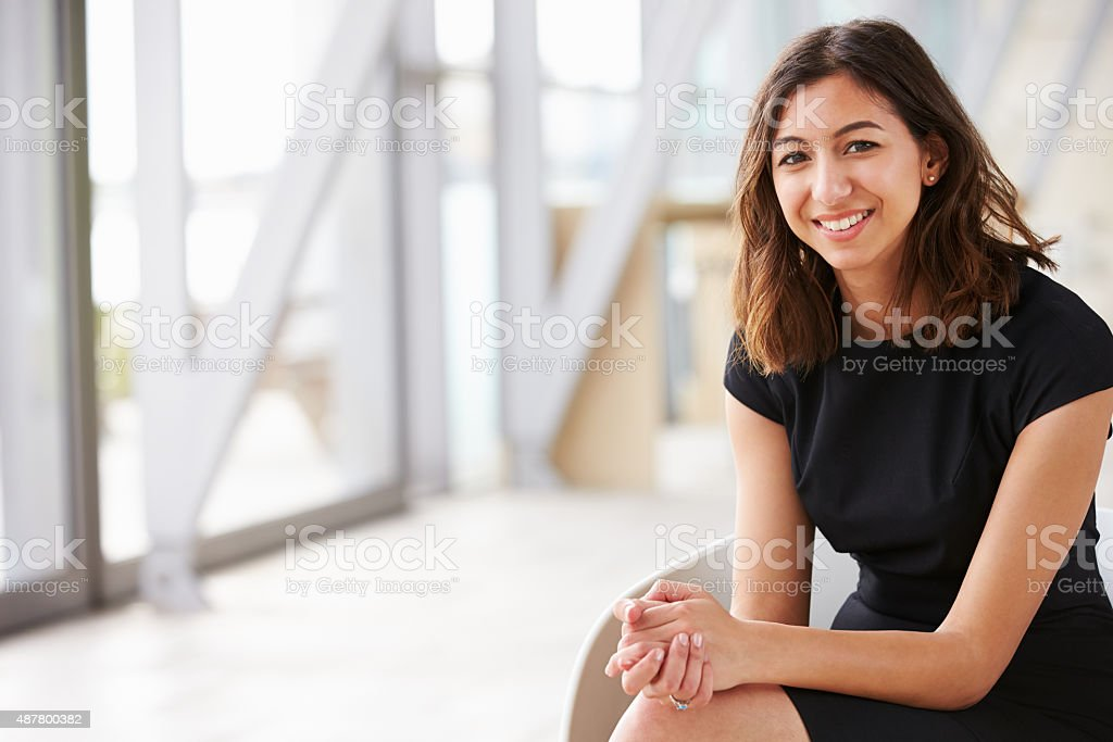 Portrait of young mixed race Asian businesswoman sitting stock photo