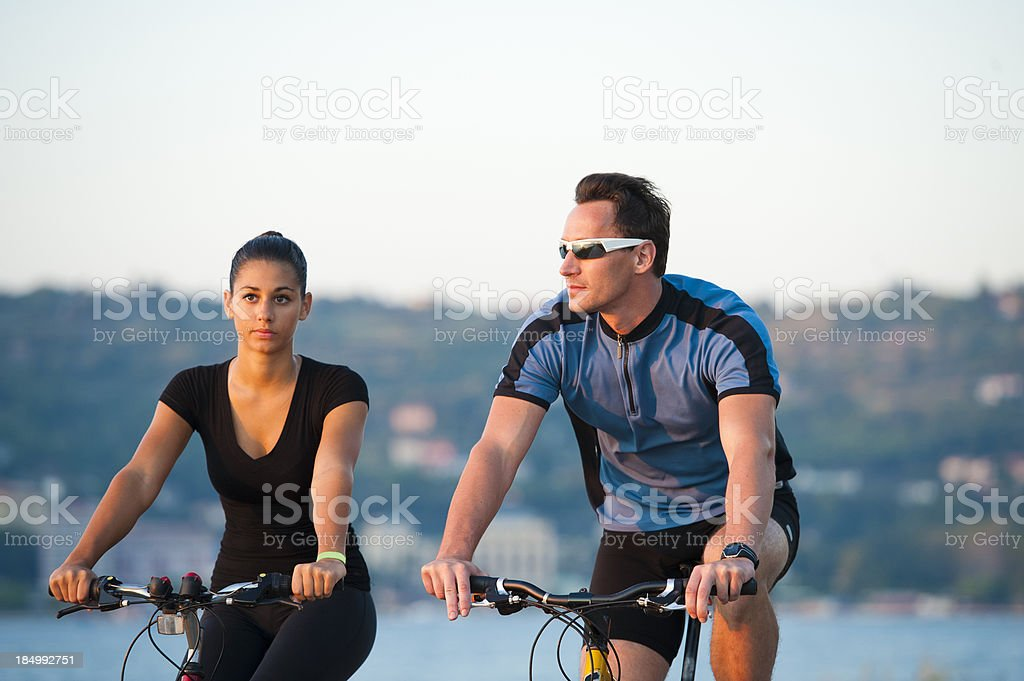 Portrait of young pair cycling by the sea royalty-free stock photo