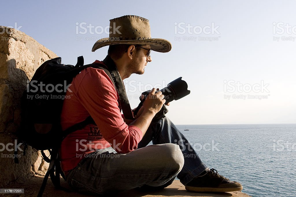 Portrait Of Young Photographer With Hat Holding Camera By Sea royalty-free stock photo