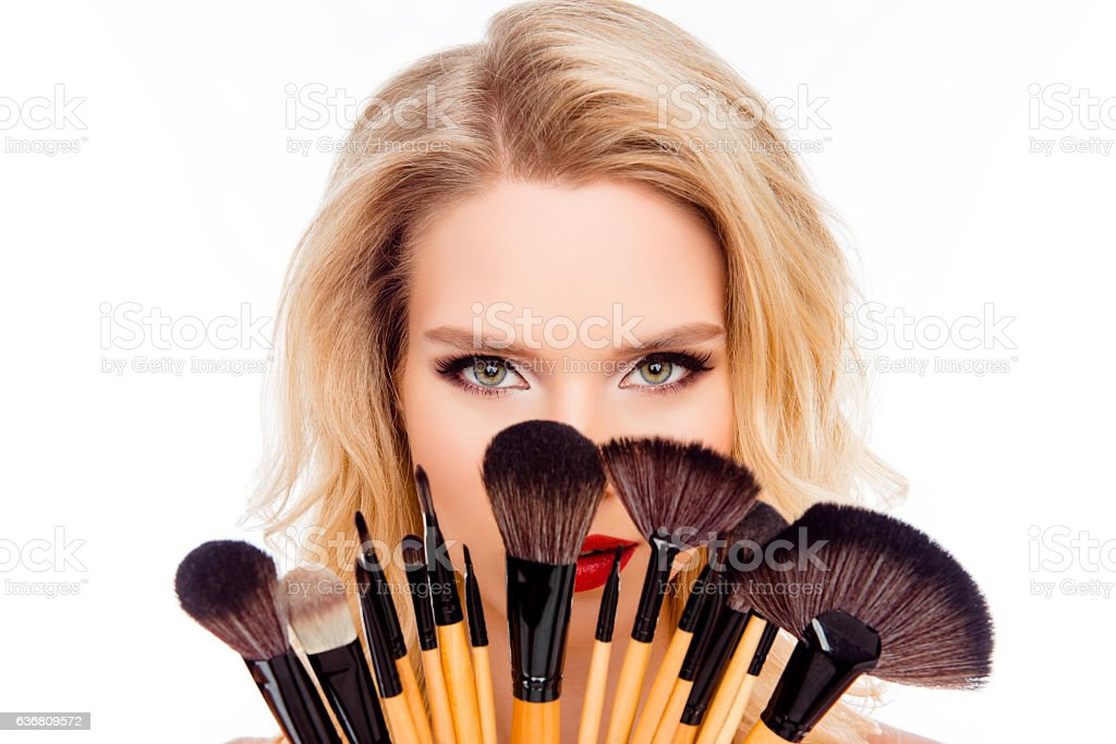 Portrait of young pretty woman hiding face behind makeup brushes stock photo