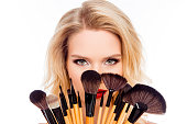 Portrait of young pretty woman hiding face behind makeup brushes