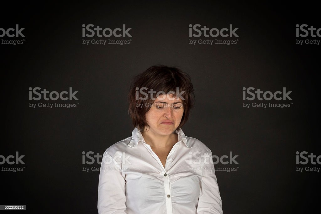 Portrait of young woman on black background. Sadness of depression...