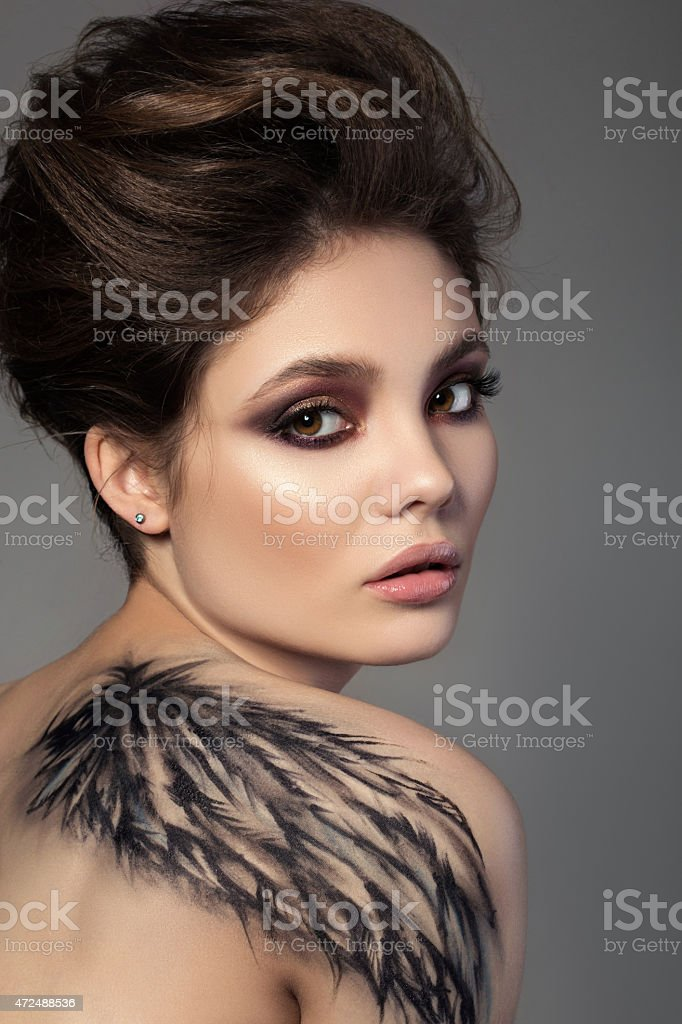 Portrait of young sensual brunette woman with black wing stock photo