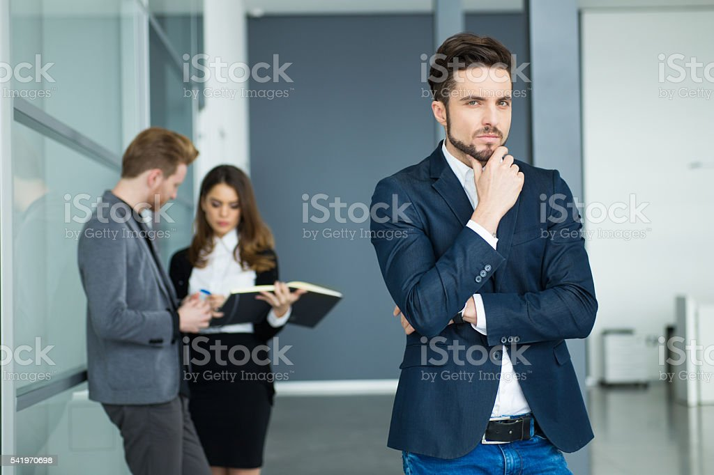 Portrait of young serious businessman with hand on chin. stock photo