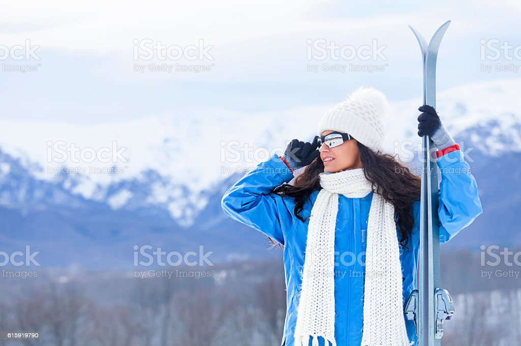 Portrait of young skier holding skis on top snow mountain stock photo