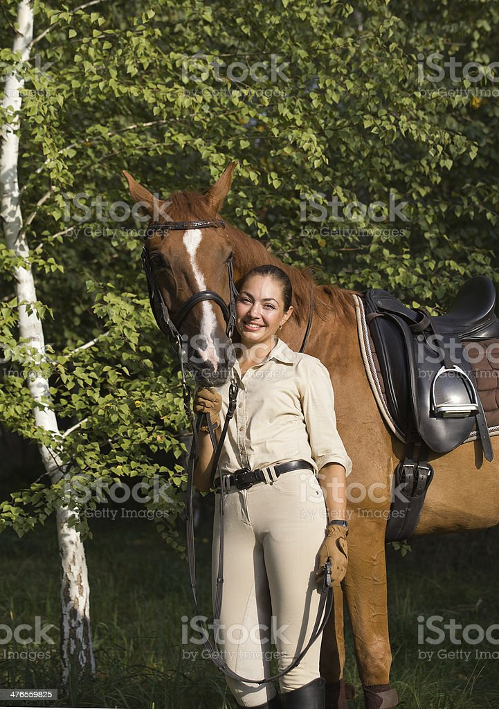 Portrait of young smiling brunette woman with a brown horse royalty-free stock photo