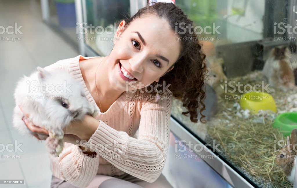 Portrait of young smiling cheerful woman holding fluffy animal in...