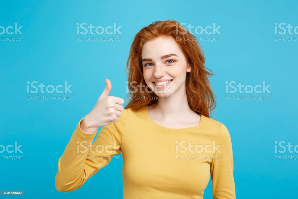 Portrait of young stylish freckled girl laughing with showing thumps up at camera. Copy space. stock photo