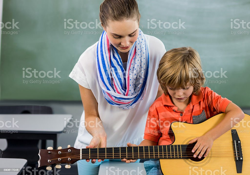 Portrait of young teacher assisting boy to play guitar stock photo