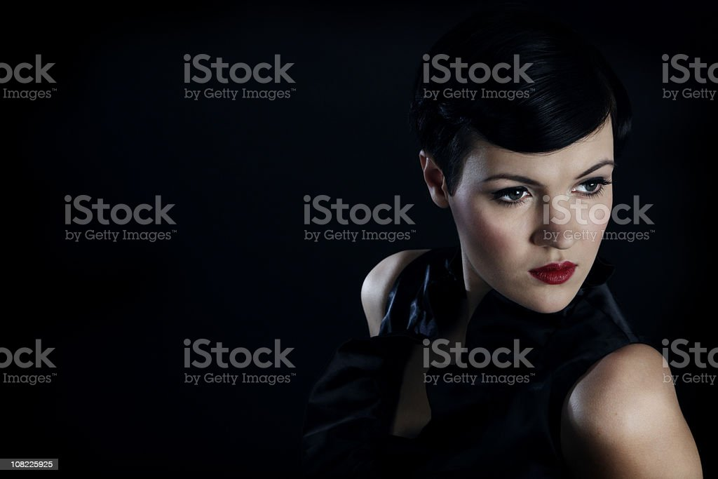 Portrait of Young Woman Against Black Background, Low Key stock photo