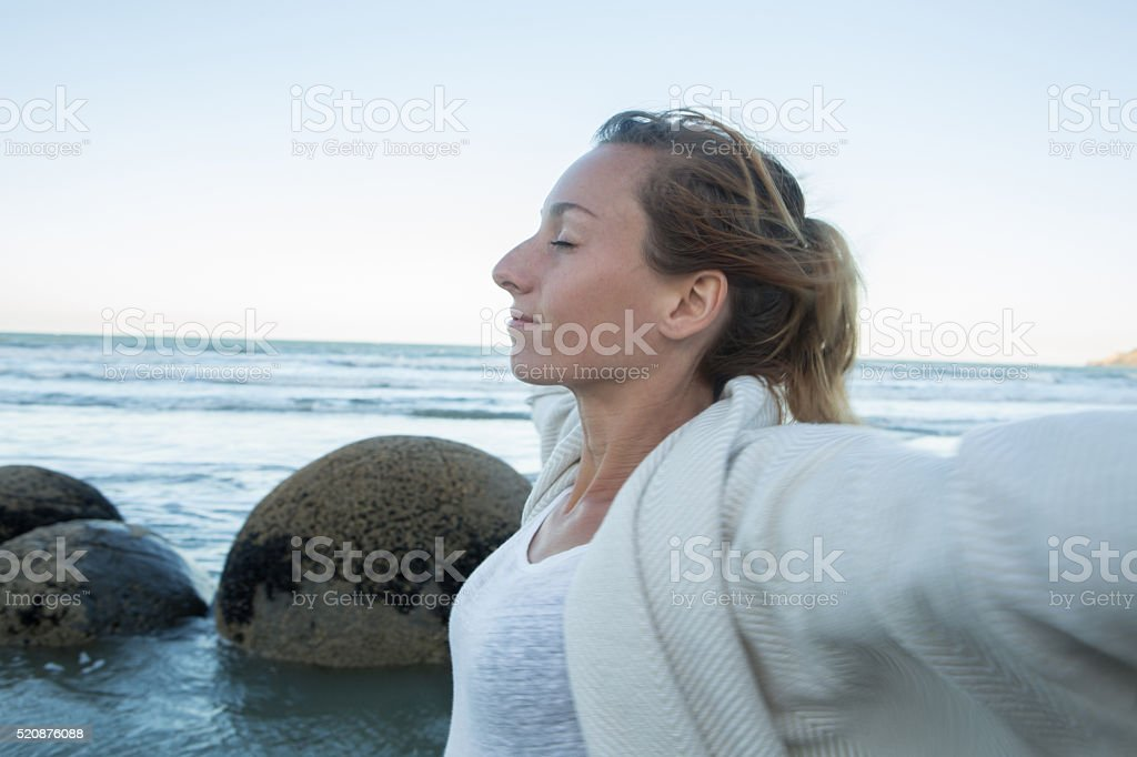 Portrait of young woman arms outstretched near spheric boulders stock photo