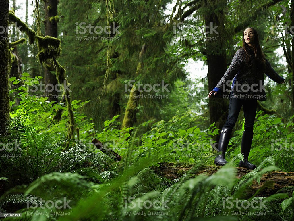 Portrait of young woman balancing on fallen tree. stock photo
