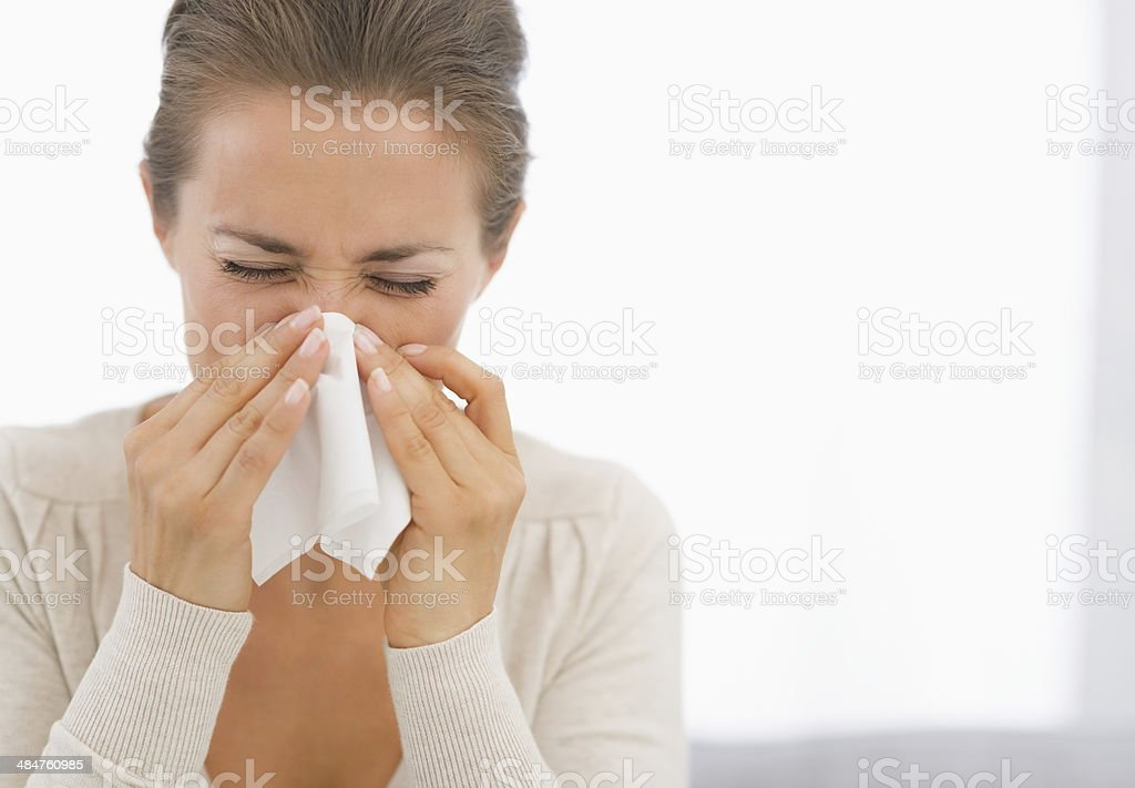 portrait of young woman blowing nose stock photo