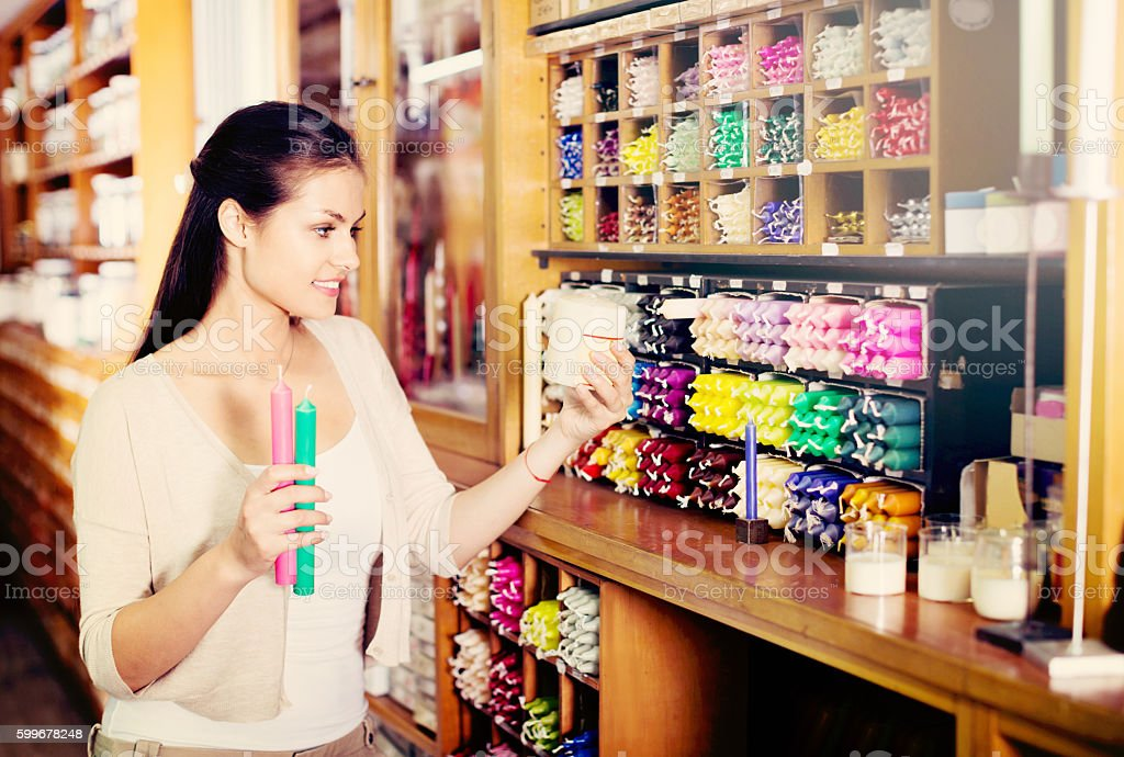 Portrait of young  woman choosing candles stock photo