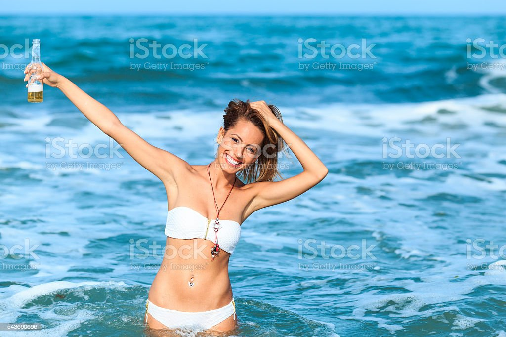 Portrait of young woman drinking beer in the sea stock photo