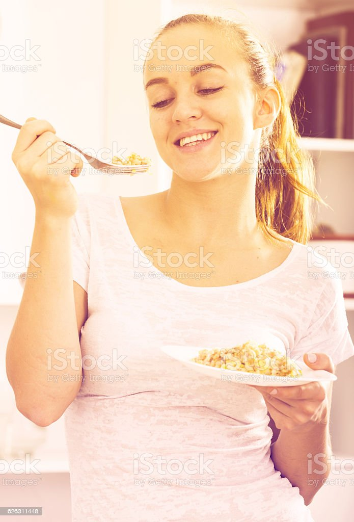 portrait of young woman eating mush at kitchen stock photo