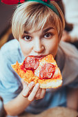 Portrait of young woman eating pizza