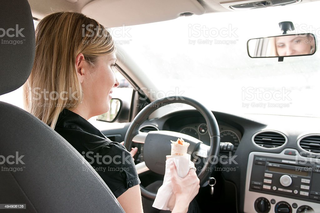 Portrait of young woman eating while driving car stock photo