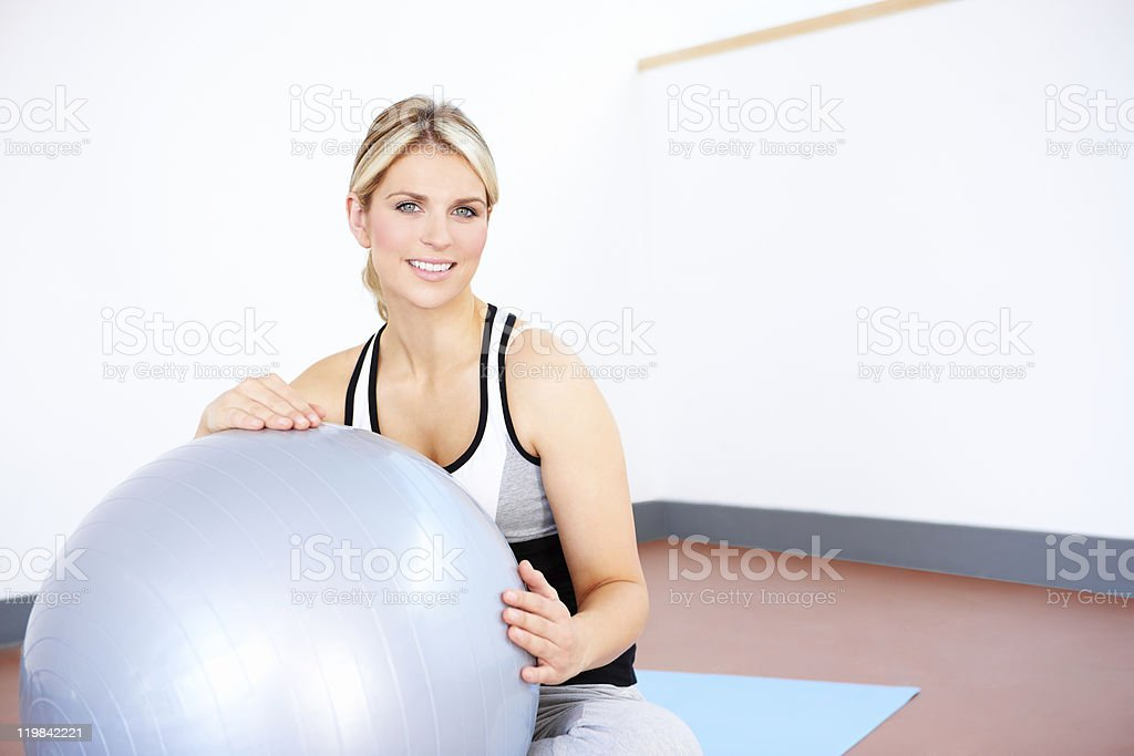 portrait of young woman exercising with fitness ball in gym stock photo