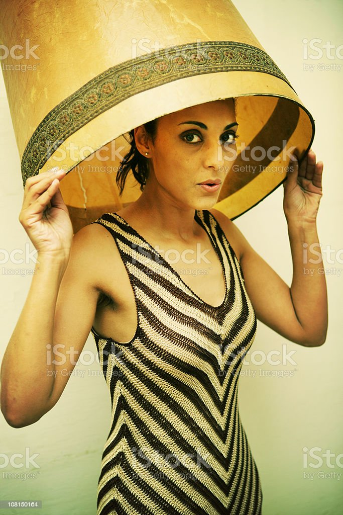 Portrait of Young Woman Hiding Under Lampshade stock photo