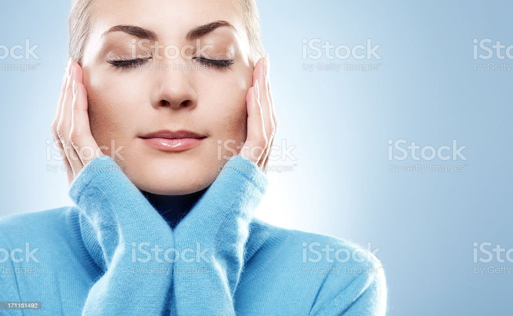 Portrait of young woman in blue jumper with eyes closed royalty-free stock photo
