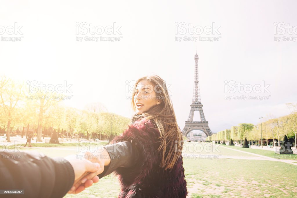 Portrait of young woman in front Eiffel tower stock photo