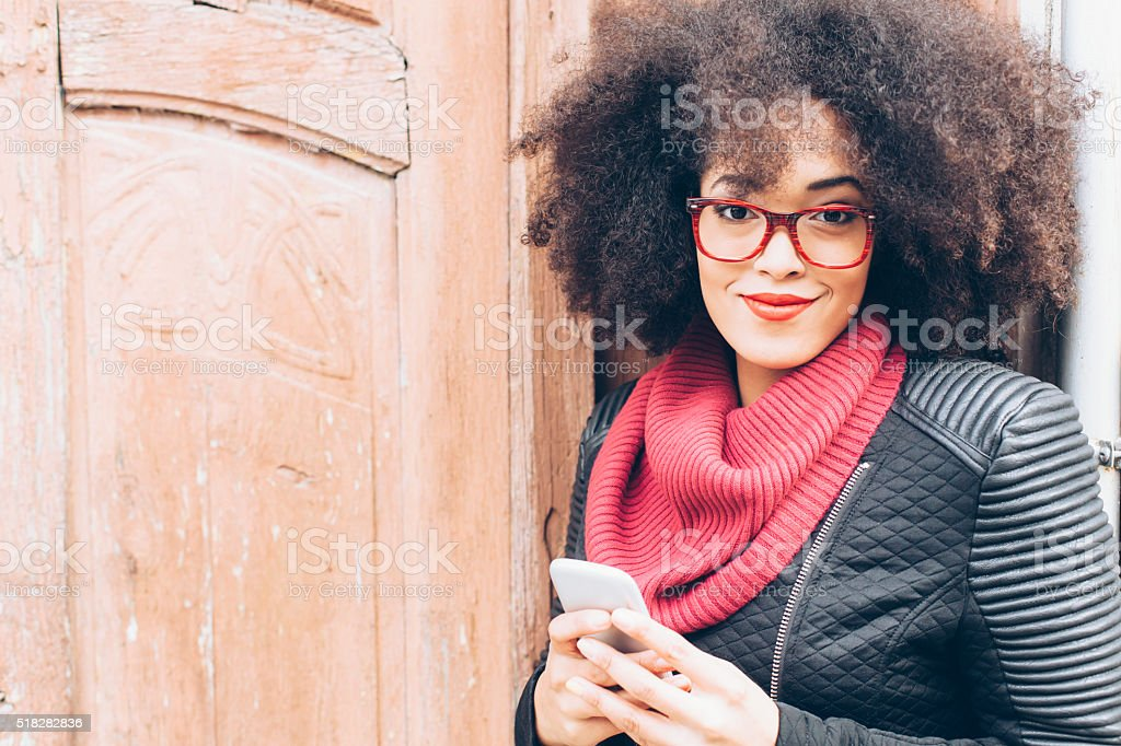 Portrait of young woman in front of a wooden door stock photo