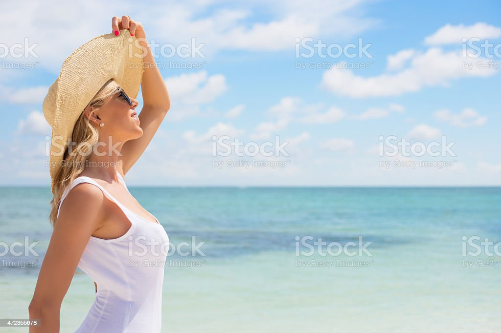 Portrait of young woman in hat enjoying sunshine at beach stock photo