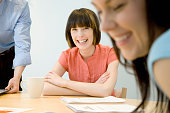 Portrait of young woman in office meeting with team