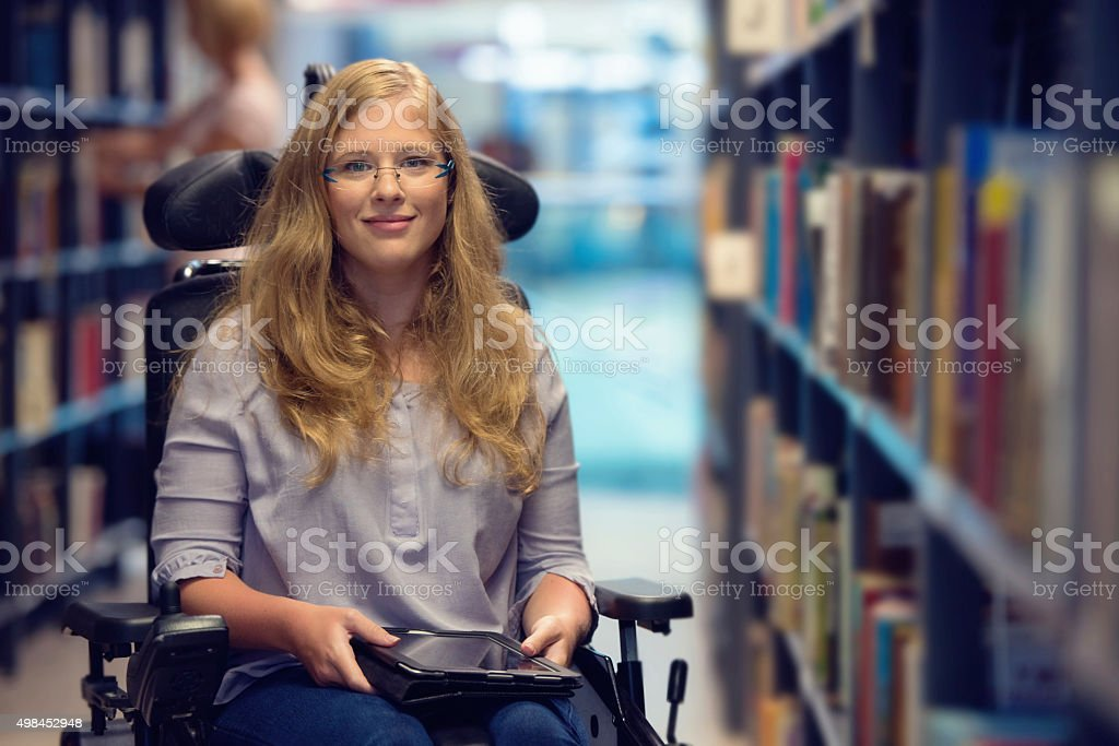 Portrait of young woman in wheelchair in library stock photo