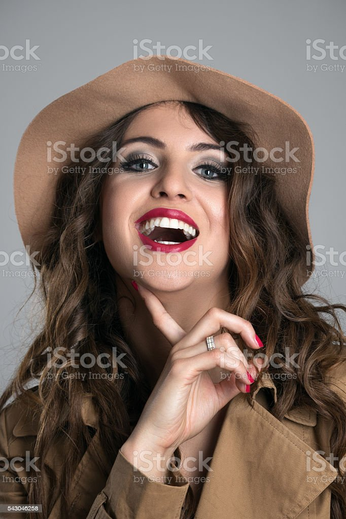 Portrait of young woman laughing with finger under her chin stock photo