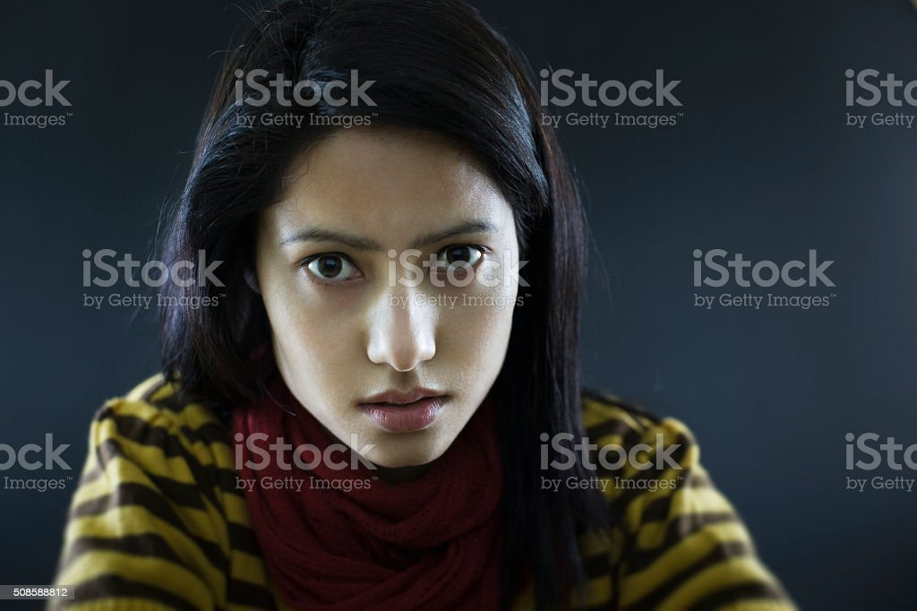 Portrait of young woman looking at camera with blank expression. stock photo