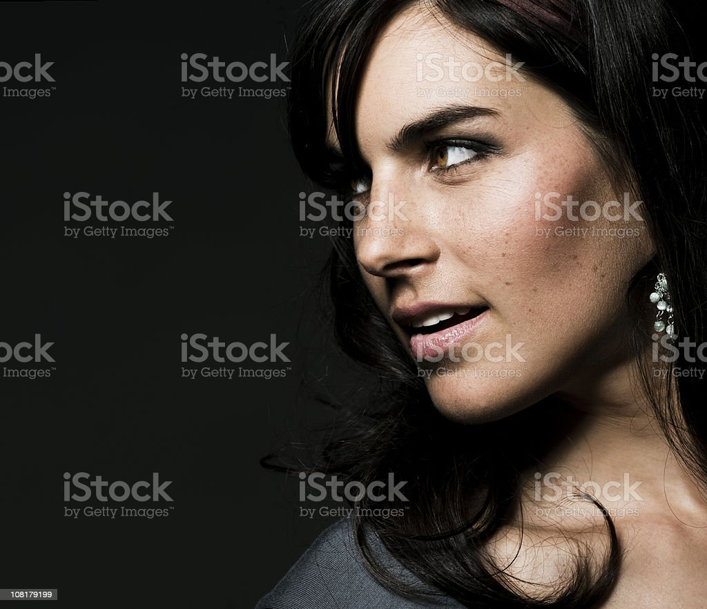 Portrait of Young Woman Looking Away on Black Background royalty-free stock photo