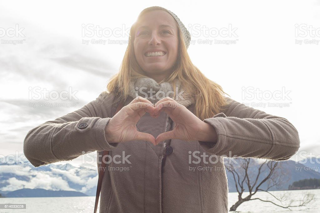 Portrait of young woman making heart shape finger frame stock photo