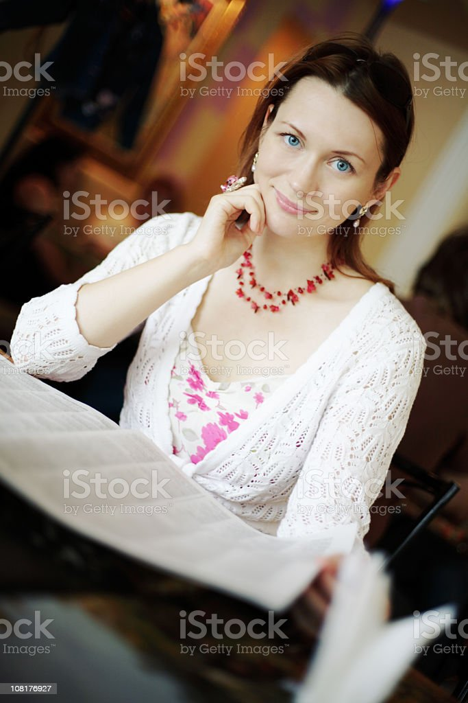 Portrait of Young Woman Reading Newspaper at Table royalty-free stock photo