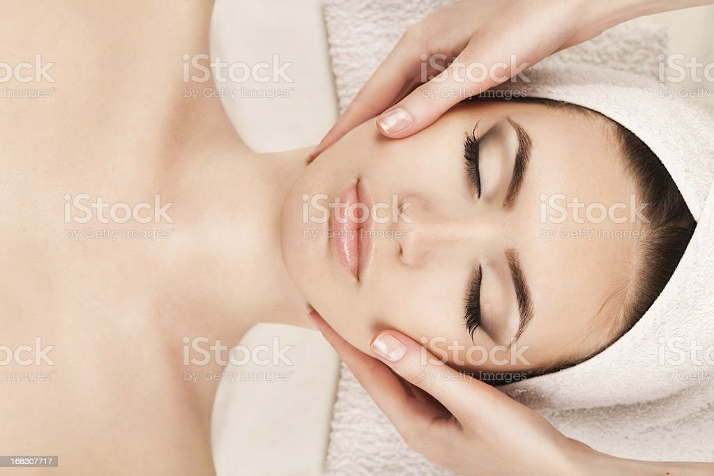 Portrait of young woman receiving facial massage royalty-free stock photo