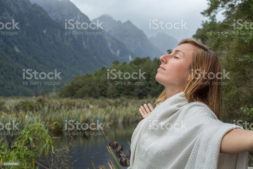 Portrait of young woman relaxing by the lake, arms outstretched stock photo