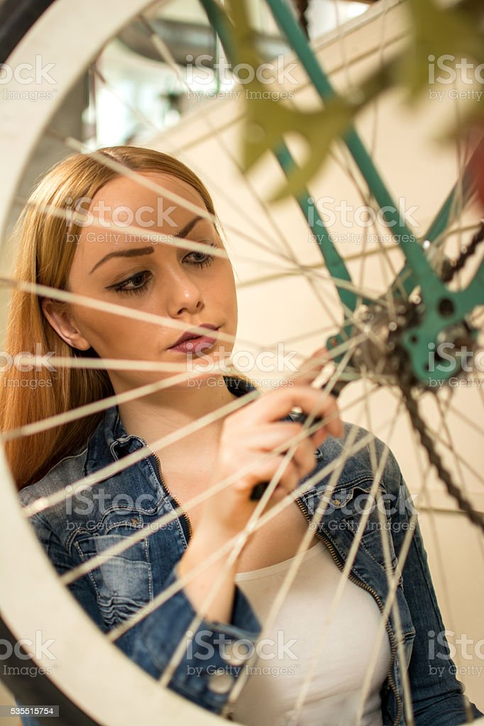 Portrait of young woman repairing her bicycle. stock photo