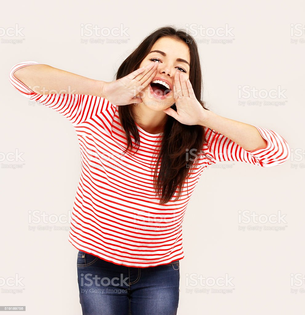 Portrait of young woman shouting at the camera.White background stock photo