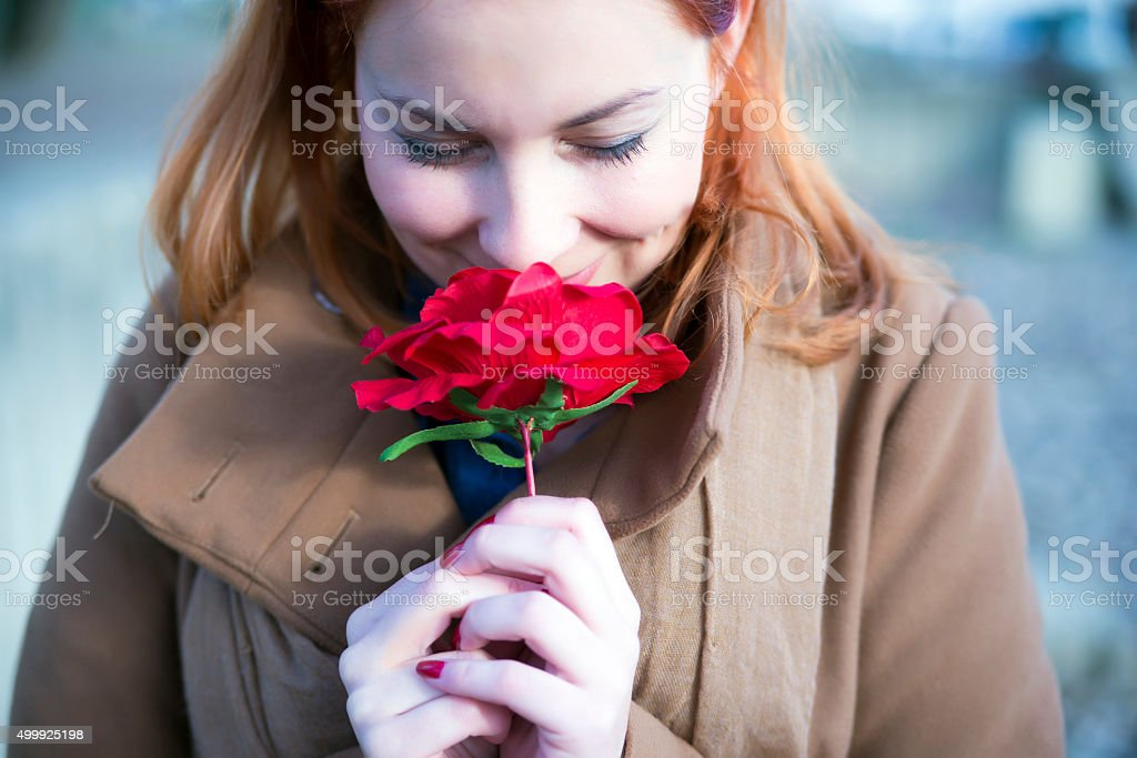 Portrait of young woman Smelling red rose flower stock photo