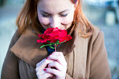 Portrait of young woman Smelling red rose flower